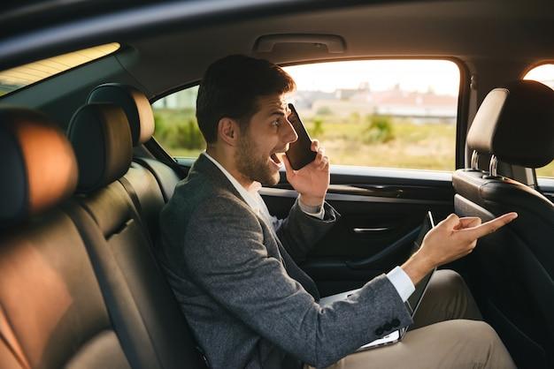 Przestraszony biznesmen rozmawia przez telefon komórkowy