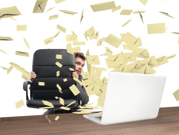 Przestraszony biznesmen ukryty za krzesłem zalanym pocztą
