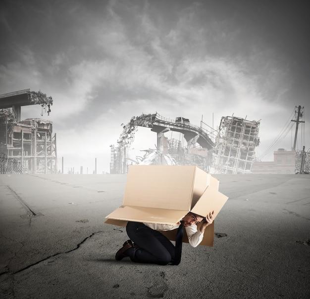 Przestraszony biznesmen ukrywa się pod kartonem w zniszczonym mieście