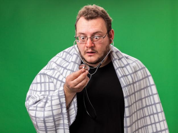 Przestraszony chory mężczyzna w średnim wieku owinięty w kratę słuchający bicia własnego serca