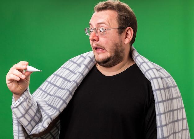 Przestraszony chory mężczyzna w średnim wieku, owinięty w szkocką kratę i patrzący na termometr