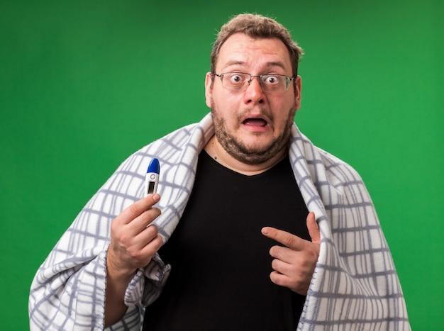 Przestraszony chory mężczyzna w średnim wieku, owinięty w szkocką kratę i wskazujący na termometr