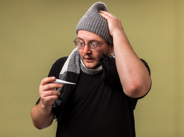 Przestraszony chory mężczyzna w średnim wieku, ubrany w zimową czapkę i szalik, trzymający i patrzący na termometr, kładący rękę na głowie