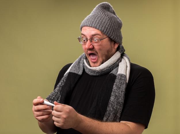 Przestraszony chory mężczyzna w średnim wieku, ubrany w zimową czapkę i szalik, trzymający i patrzący na termometr