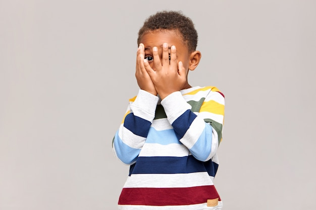 Przestraszony ciemnoskóry chłopiec zakrywający twarz obiema rękami, jakby bał się zobaczyć coś strasznego, szpiegując przez dziurę między palcami. nieśmiałe afrykańskie dziecko ukrywa się lub bawi w chowanego
