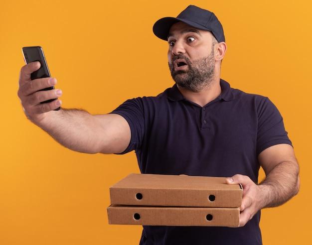 Przestraszony Doręczyciel W średnim Wieku W Mundurze I Czapce Trzymający Pudełka Po Pizzy Robi Selfie Na żółtej ścianie Darmowe Zdjęcia