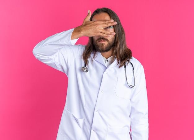 Przestraszony dorosły mężczyzna lekarz ubrany w szatę medyczną i stetoskop w okularach trzymających rękę przed oczami, patrząc na kamerę między palcami odizolowanymi na różowej ścianie