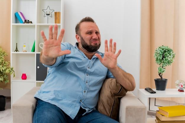 Przestraszony dorosły mężczyzna słowiański siedzi na fotelu wyciągając ręce patrząc na kamerę w salonie
