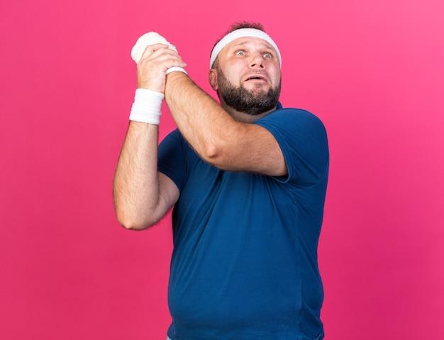Przestraszony dorosły słowiański sportowy mężczyzna z opaską na głowę i opaskami na nadgarstek, trzymający rękę i patrząc w górę odizolowany na różowej ścianie z miejscem na kopię
