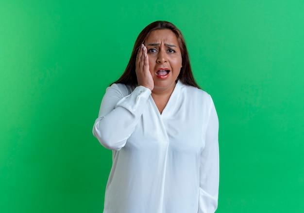 Przestraszony dorywczo kaukaski kobieta w średnim wieku, kładąc rękę na policzku na białym tle na zielonej ścianie
