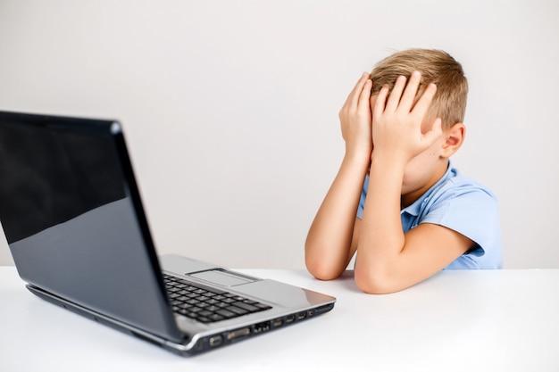 Przestraszony dzieciak zasłaniający twarz biurkiem z laptopem