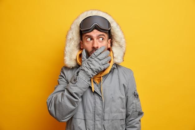 Przestraszony emocjonalnie snowboardzista zakrywa usta, próbując ukryć tajemnicę, nosi ciepłe rękawiczki i szarą kurtkę termiczną.