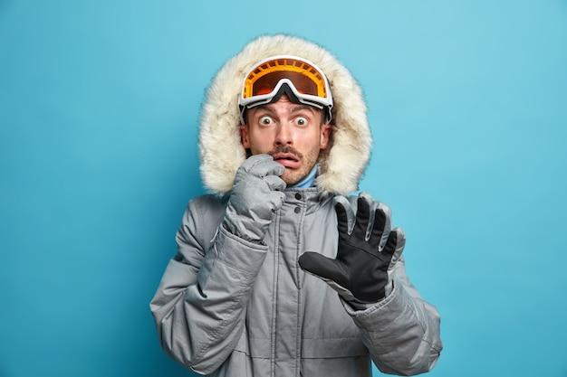 Przestraszony, emocjonalny narciarz nosi ciepłą kurtkę, gogle narciarskie i rękawiczki, patrzy zszokowany, że aktywny zimowy urlop spędza wakacje w górach.