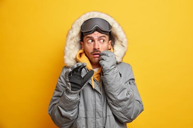 Przestraszony europejczyk w odzieży wierzchniej z futrzanym kapturem odpoczywa w górach uprawia sporty ekstremalne, aktywnie spędzając czas w zimnych porach roku.