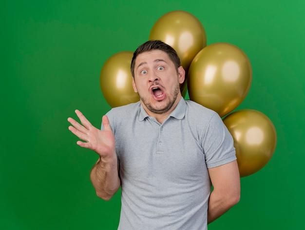 Przestraszony facet młody imprezowicz w czapce urodzinowej stojącej przed balonami, rozkładając rękę na białym tle na zielono