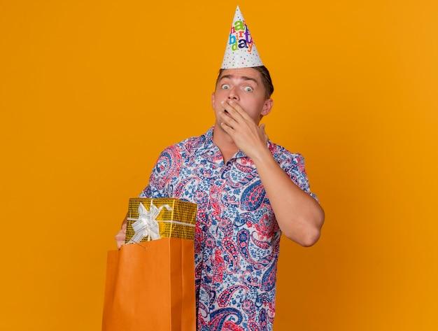 Przestraszony facet młody imprezowicz w czapce urodzinowej, trzymając torbę na prezent i zakrytą twarz ręką odizolowaną na pomarańczowo