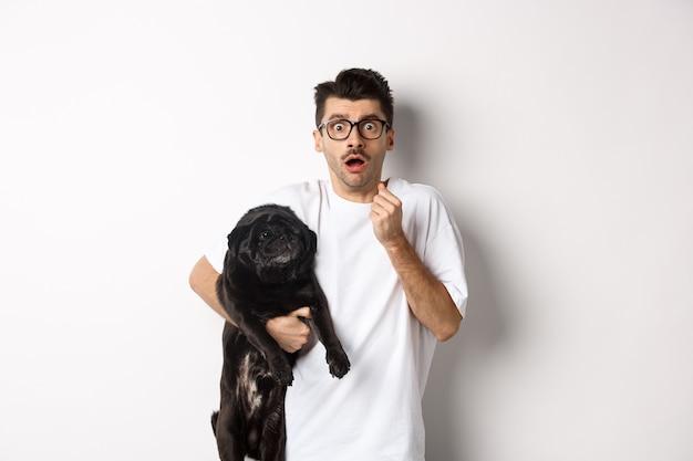 Przestraszony hipster przytulający swojego czarnego szczeniaka i przestraszony wpatrując się w kamerę. właściciel psa wygląda na zszokowanego, trzymając mopsa, stojącego nad białym.