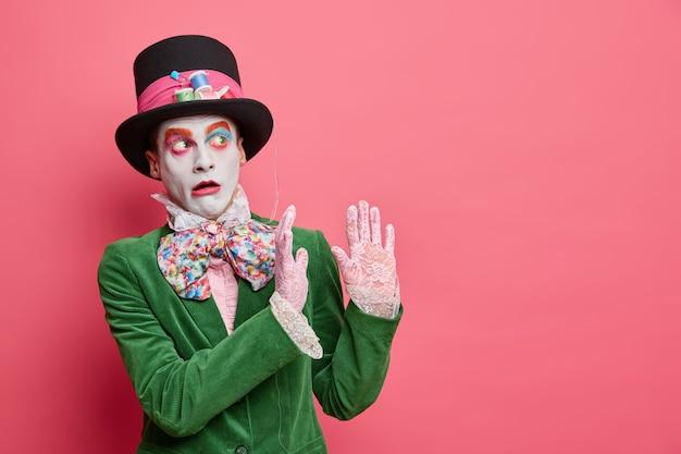 Przestraszony kapelusznik wykonuje gest obronny, boi się czegoś spadającego z wysokości, nosi koronkowe rękawiczki z dużym kapeluszem i zieloną aksamitną kurtkę pozuje na różowej ścianie z pustą przestrzenią
