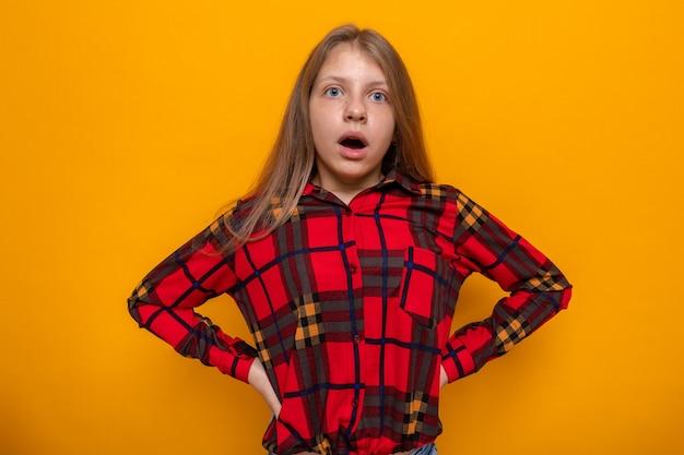 Przestraszony kładąc ręce na biodrze piękna mała dziewczynka ubrana w czerwoną koszulę