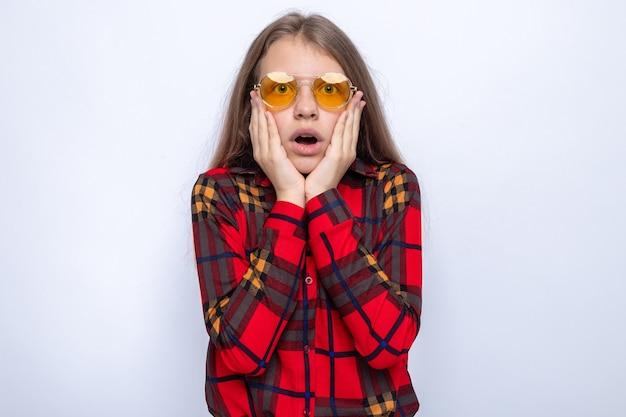 Przestraszony kładąc ręce na policzkach piękna mała dziewczynka ubrana w czerwoną koszulę i okulary