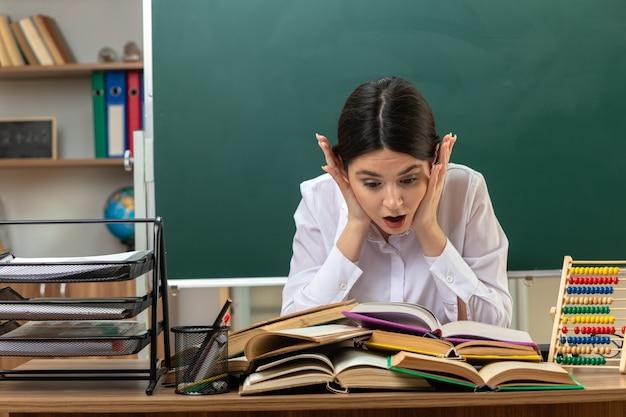 Przestraszony kładąc ręce na policzku młoda nauczycielka czytająca książkę na stole siedzącym przy stole z szkolnymi narzędziami w klasie