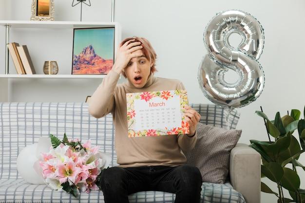 Przestraszony, kładąc rękę na czole, przystojny facet na szczęśliwy dzień kobiet, trzymając kalendarz, siedząc na kanapie w salonie