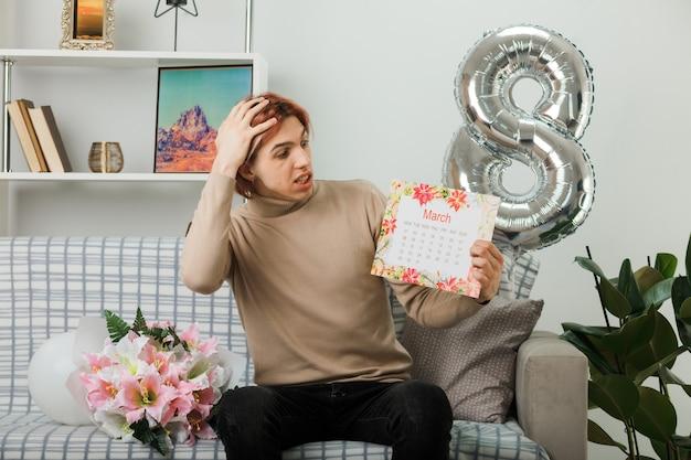 Przestraszony, kładąc rękę na głowie, przystojny facet na szczęśliwy dzień kobiet, trzymając i patrząc na kalendarz, siedząc na kanapie w salonie
