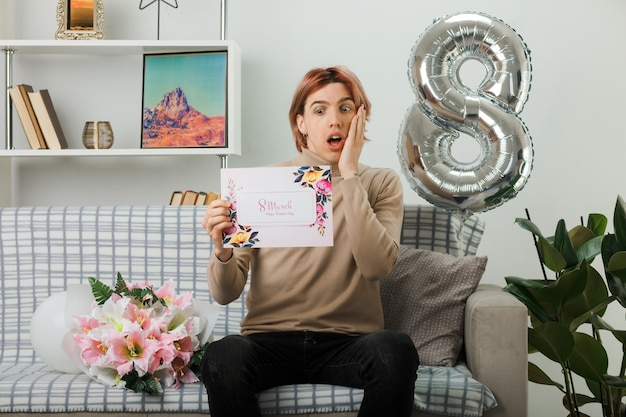 Przestraszony, kładąc rękę na policzku, przystojny facet na szczęśliwy dzień kobiet, trzymając kartkę z życzeniami, siedząc na kanapie w salonie