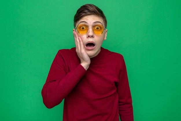 Przestraszony kładzenie dłoni na policzku młody przystojny facet w okularach odizolowanych na zielonej ścianie