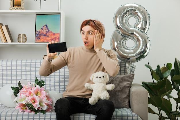 Przestraszony kładzenie dłoni na policzku przystojny facet na szczęśliwy dzień kobiet trzymający misia z telefonem siedzącym na kanapie w salonie