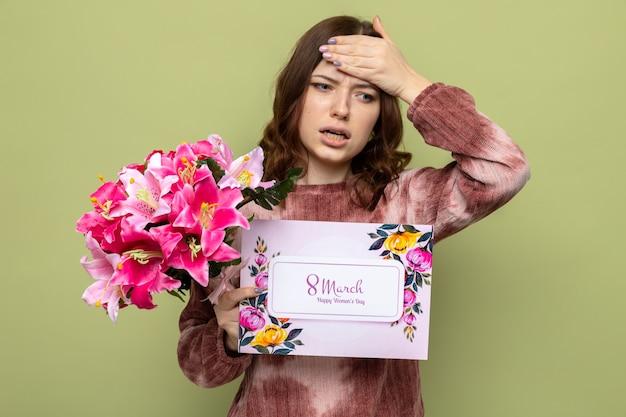 Przestraszony kładzenie ręki na czole piękna młoda dziewczyna na szczęśliwy dzień kobiet trzyma bukiet z kartką z życzeniami