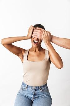 Przestraszony krzyczący młoda afrykańska kobieta siedzi, podczas gdy ręka mężczyzny coning jej oczy na białym tle