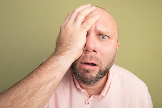 Przestraszony łysy mężczyzna w średnim wieku ubrany w różową koszulkę zakrył oko ręką