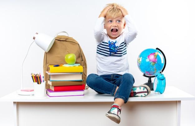 Przestraszony mały chłopiec szkolny siedzący na stole z szkolnymi narzędziami chwycił głowę