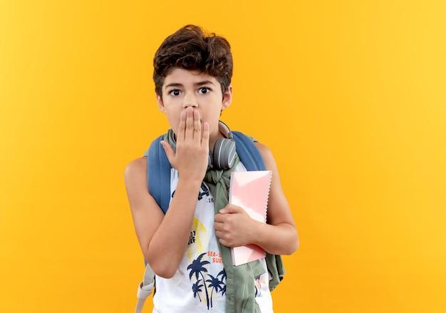 Przestraszony mały chłopiec w szkole noszenie plecaka i słuchawek, trzymając notebook i zakryte usta ręką na żółtym tle