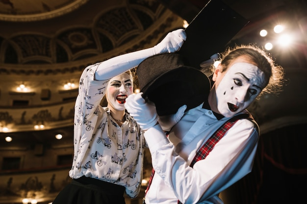 Przestraszony mężczyzna mime broniąc się przed mim kobieta uderzając ze schowka