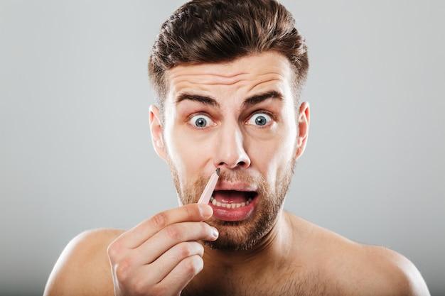 Przestraszony mężczyzna usuwa włosy za pomocą pincety