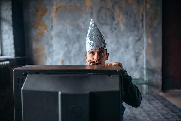 Przestraszony mężczyzna w czapce z folii aluminiowej ogląda telewizję, ufo