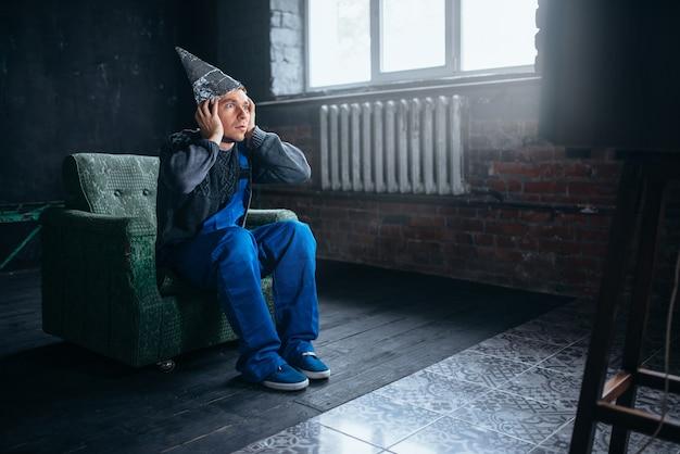 Przestraszony mężczyzna w czapce z folii aluminiowej oglądać telewizję, ochrona umysłu, koncepcja paranoi. ufo, teoria spiskowa, fobia telepatyczna