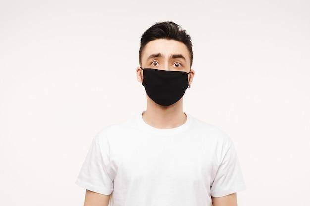 Przestraszony mężczyzna w masce medycznej wygląda w aparacie. przestraszony młody człowiek w obawie przed koronawirusem w białej koszulce i ochronnej masce medycznej przed wirusami