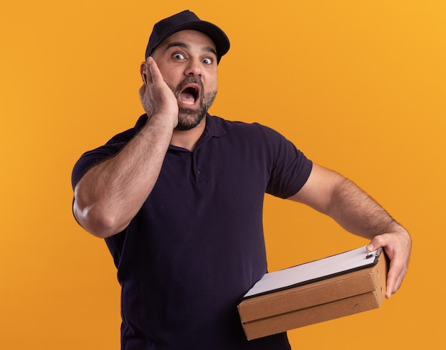 Przestraszony mężczyzna w średnim wieku dostawy w mundurze i czapce, trzymając schowek z pudełkami po pizzy, kładąc dłoń na policzku na białym tle na żółtej ścianie