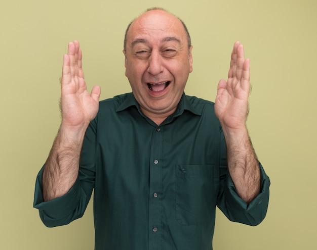 Przestraszony mężczyzna w średnim wieku ubrany w zielony t-shirt pokazujący rozmiar na białym tle na oliwkowej ścianie