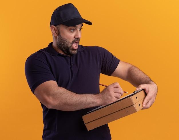 Przestraszony mężczyzna w średnim wieku w mundurze i czapce piszący coś w schowku na pudełkach po pizzy na białym tle na żółtej ścianie