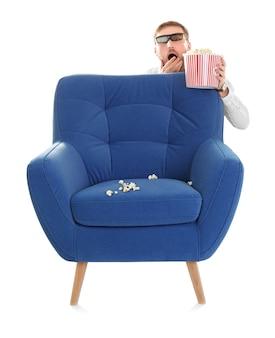 Przestraszony mężczyzna z okularami 3d i popcornem chowającym się za fotelem podczas pokazu kinowego