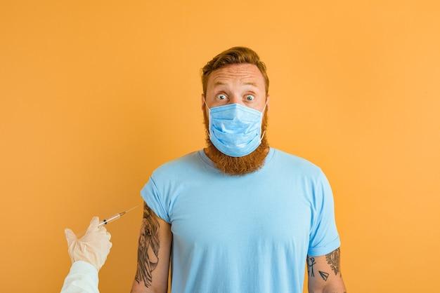 Przestraszony mężczyzna z tatuażem na brodzie i maską na covid jest gotowy na szczepionkę wirusową