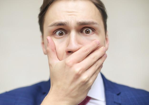 Przestraszony mężczyzna, zakrywający usta dłonią