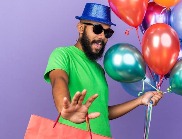 Przestraszony młody afro-amerykański facet w kapeluszu imprezowym w okularach, trzymający balony z torbą prezentową pokazującą gest zatrzymania na białym tle na niebieskiej ścianie