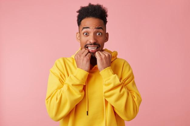 Przestraszony młody afroamerykanin w żółtej bluzie z kapturem, z przerażeniem patrzy z szeroko otwartymi oczami i zaciska zęby, obgryza paznokcie, stoi.