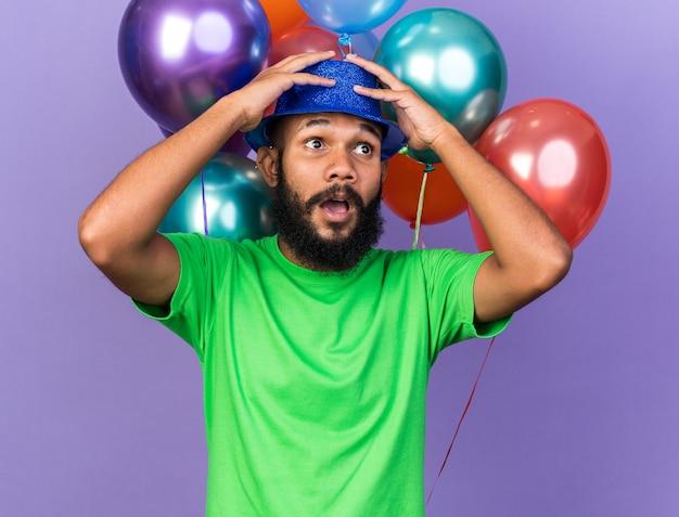 Przestraszony młody afroamerykański facet w imprezowym kapeluszu stojący przed balonami chwycił głowę odizolowaną na niebieskiej ścianie