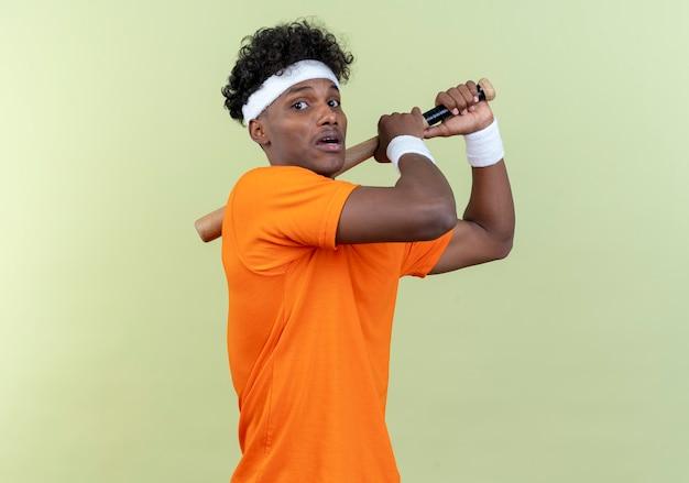 Przestraszony młody afroamerykański sportowy mężczyzna ubrany w opaskę i opaskę, trzymając nietoperza na ramieniu na białym tle na zielonej ścianie